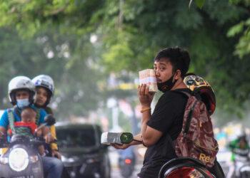 PENUKARAN UANG - Seorang warga tengah menunggu pengendara sambil menawarkan penukaran uang di jalan Diponegoro, Kota Padang, Minggu (2/5). Menjelang lebaran, jasa penukaran uang kertas mulai menjamur di sejumlah titik di kota Padang. TIO FURQAN
