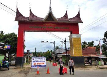 Dua polisi tetap berjaga di gerbang menuju Lembah Harau, kendati sudah ada pengumuman kawasan wisata ini ditutup. RAKHMATUL AKBAR